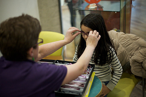Photo. Orthoptist positioning frames on young girl.
